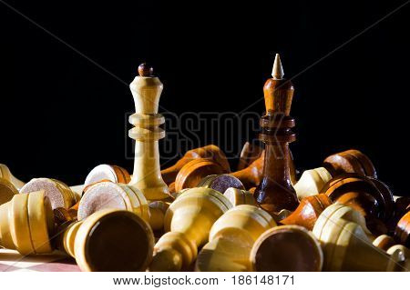 White queen and black king among fallen chess pieces on chessboard with dark background