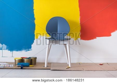empty chair and equipment for painting in front of colorful wall in the background