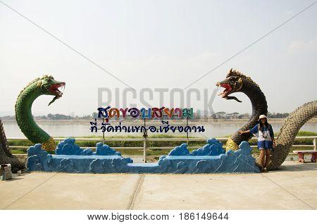 Travelers Thai Woman Visit And Posing For Take Photo With Black Naga Statue At Mae Khong Riverside