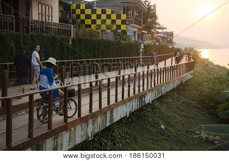 Asian Thai Woman Riding Bicycle And Travelers People Walking Relax On The Road At Riverside Mekong R