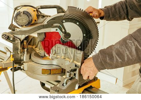 Man working with circular saw, selective focus Circular Saw. Cutting a wooden plank