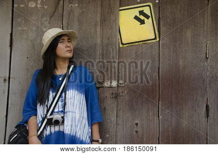 Asian thai woman traveler visit and posing for take photo with old wooden door retro style on street night market at Chiang Khan on February 21 2017 in Loei Thailand
