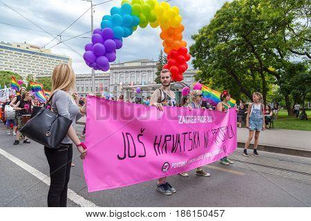 ZAGREB, CROATIA - JUNE 11, 2016: 15th Zagreb pride. LGBTIQ activists holding pride banner.