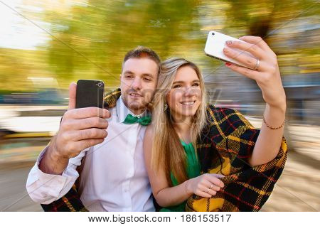Beautiful young couple taking photos with mobile