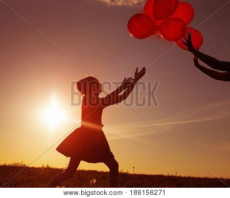 the girl with red balloons at sunset