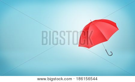 An open classic red umbrella with a handle vertically placed on blue background. Rainy weather. Protection and safety. Umbrellas and parasols.
