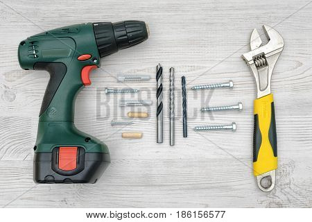 A cordless drill, a wrench, several drill bits, screw bolts and dowels on light wood background. Tools and equipment. Hardware store. Hand-made and renovation.