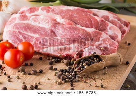 Few Pork Steaks From Neck With Color Pepper In Spoon