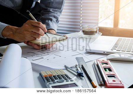 Engineerman writing notebook on office desk table with architecture blue print close up. Buliding concept.