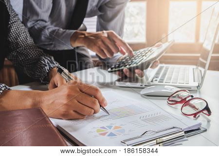 Image of two young business team using calculator and graph financia at meeting.Close up business team analysis and strategy concept.