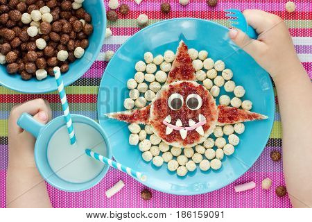 Child eat funny breakfast from toast with jam shaped shark cereal balls and milk