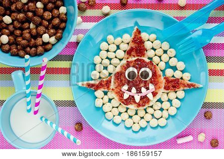 Creative food idea for fun breakfast - shark toast with strawberry jam chocolate eyes and candy teeth swims in sea of cereal balls
