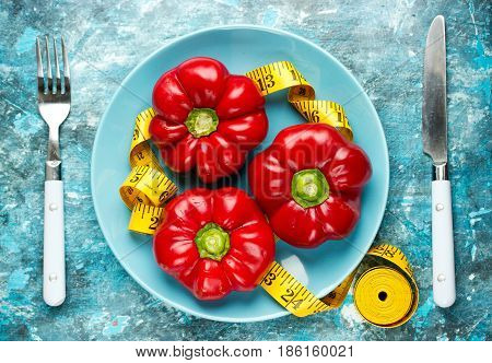 Red pepper and measuring tape on plate diet concept