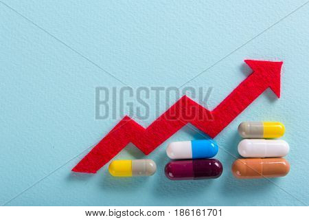 Colored pills capsules with medications. Increase the dosage of the medicine. Growing diagram up with a red arrow.