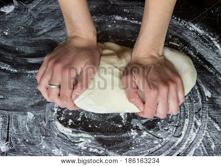 girl's hands knead yeast dough on wooden table