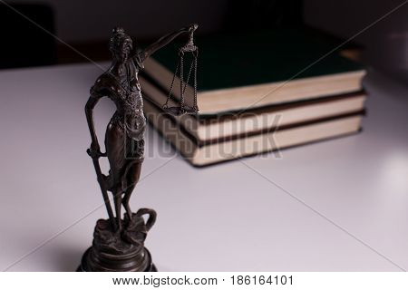 Themis on a white table against the background of the books.