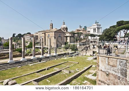 Rome, Italy - March 12, 2017 : View on antique  forum columns and ruins of famous ancient Roman Forum on the background of bright blue sky, Rome, Italy