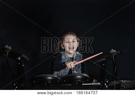 Little caucasian girl drummer playing the elettronic drum kit on black background.