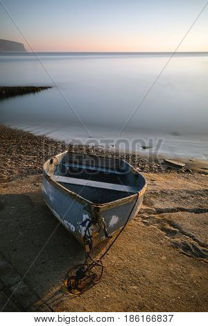 Beautiful Vibrant Long Exposure Landscape Image Of Old Rowing Boat On Slipway At Sunrise