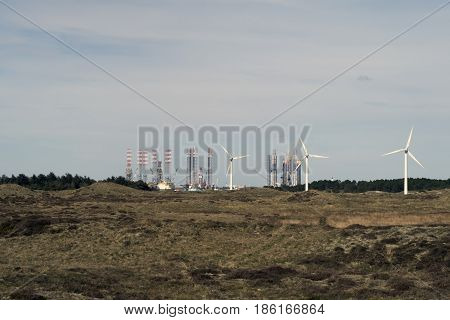 Three wind turbines on Fanø with oil platforms in Esbjerg in the background Denmark