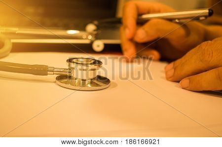 Stethoscope on paper and using screen tablet laptop computer at medicine doctor work selective focus classic tone