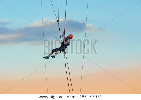 young beautiful brave woman roupejumping in the evening on the bridge