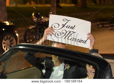 A newlywed couple is driving a convertible modern car on a road for their honeymoon. The bride is driving and the husband holding a just married placard front view