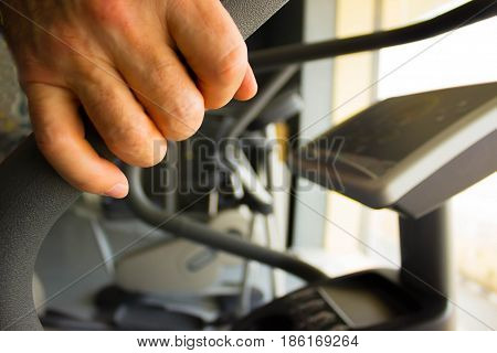 The abstract fitness gym background. Selective focus on Handle simulator with male hand