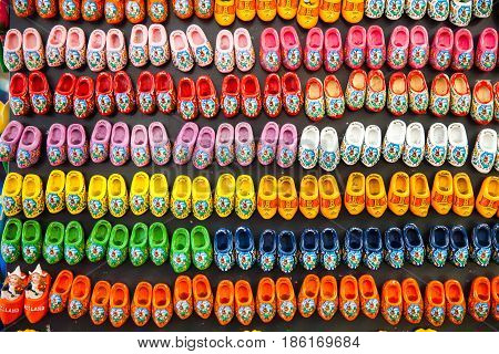 Background of different colors wooden clogs - magnet souvenirs, traditional Holland shoes