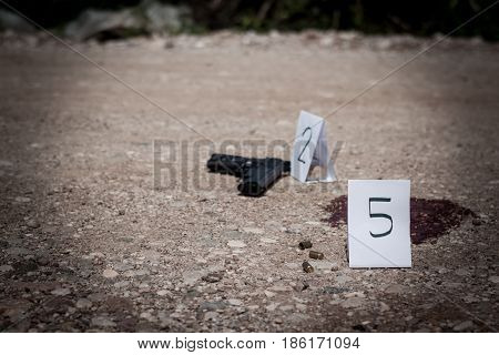 The crime scene murder investigation gun and shell finds the police puts tags rip shells and guns traces of blood gore crime scene investigation