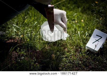 The Crime Scene, Murder, Investigation, Police Found A Bloody Knife In The Grass And Taken As Eviden