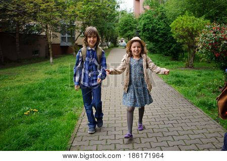Elementary school students hurry to school. Schoolboy and schoolgirl with backpacks behind the back go to the lesson. poster