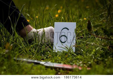 The crime scene murder investigation bloody knife on the grass an investigation is underway expert witness with gloves puts labels on the crime scene