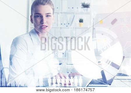 Portrait of a serious blond businesswoman at her workplace in an office. She is sitting at a laptop and looking at the viewer. Toned image double exposure
