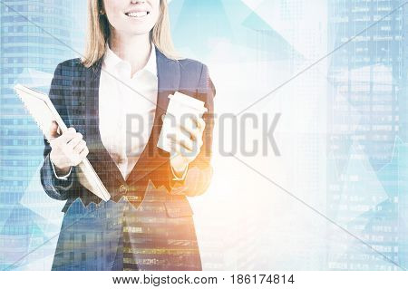 Portrait of an unrecognizable businesswoman with a coffee to go and a notebook standing against a city panorama. Toned image double exposure mock up