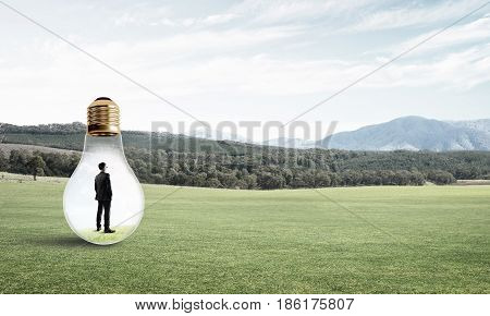 Young businessman trapped inside of light bulb on grass