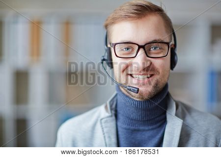 Helpdesk consultant with headset looking at camera