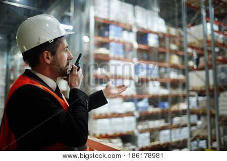 Worker with talkie-walkie reporting something important to managers