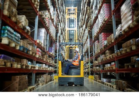 Worker in forklift-truck loading packed goods