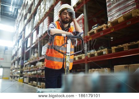 Tired worker with forklift touching his forehead