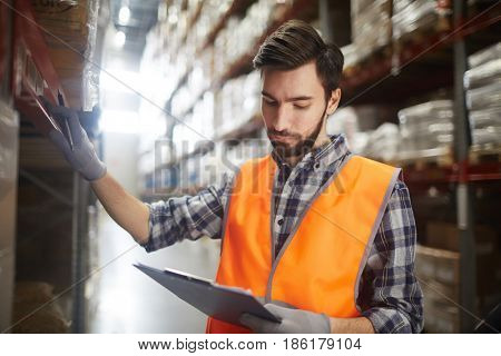Serious warehouse worker checking up goods on shelves