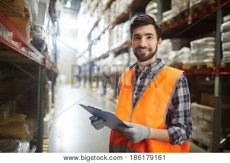 Young supervisor with document making revision of goods in storehouse