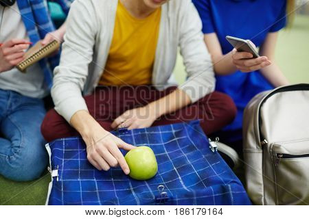 Green apple on blue piece of fabric and student explaining physical rule