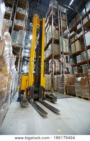 Forklift in aisle of large-scale warehouse