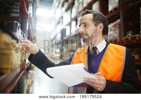 Warehouse worker with document looking through packed goods on shelf