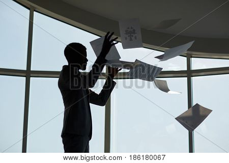 Ecstatic or irritated businessman throwing papers upwards