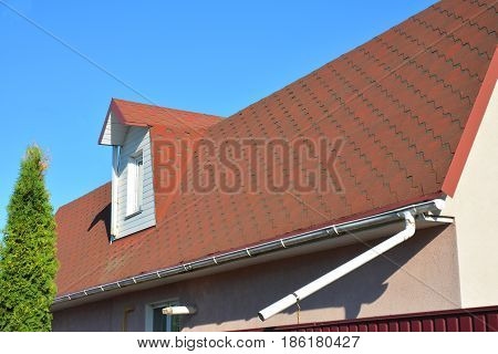 Roof Asphalt Shingles with Moss. Rain Gutter Pipeline with Downspout Pipe and Attic Mansard Window. Roofing Construction Roofing Repair.