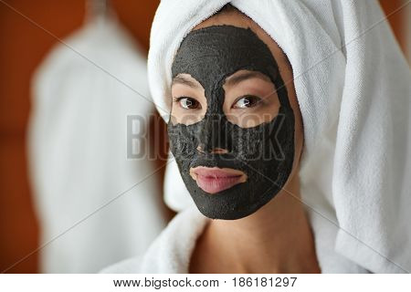 Asian woman applying face mask during beauty treatment routine