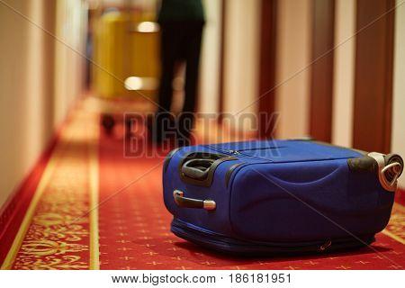 Closeup shot of bellboy carrying luggage in hotel hallway, focus on blue suitcase on floor by room door
