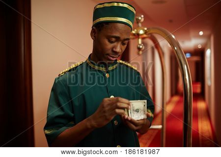 Portrait of young African boy working as bellhop in luxury hotel, counting cash from tips